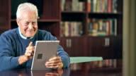 Senior man using digital tablet video
