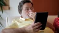 Senior man using electronic tablet video