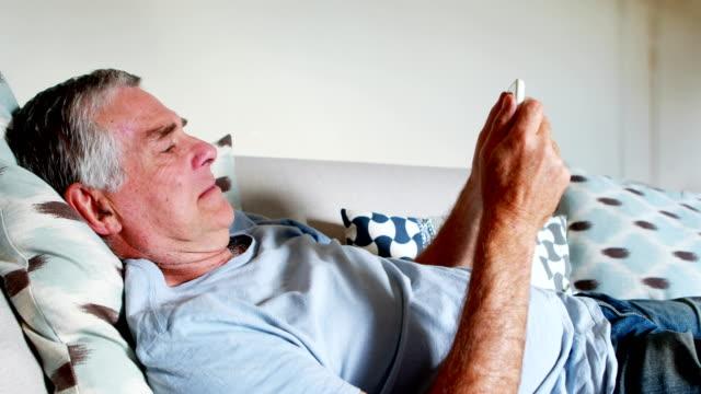 Senior man using mobile phone in bedroom 4k video