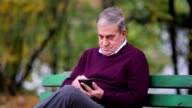 Senior man using smartphone in the park video