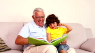Senior man with his grandson looking at photo album video
