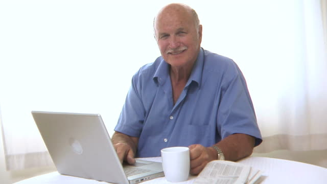 Senior man with laptop and newspaper video