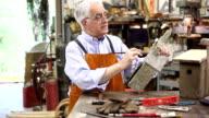 Senior man working alone in his workshop. video