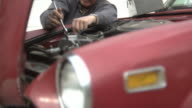 Senior man working on car engine video