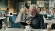 Senior man working on digital tablet in restaurant video