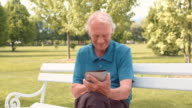 Senior man working on his tablet in the park video