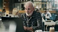 Senior man working on laptop in restaurant video