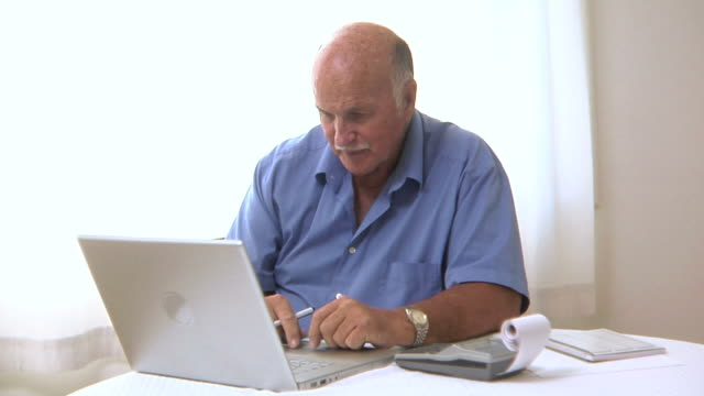 Senior man works on personal finances video