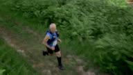 AERIAL Senior marathon participant running through forest video