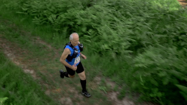 AERIAL Senior marathon participant running through forest video