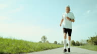 SLO MO TS Senior marathon runner running on sunny day video