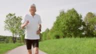 SLO MO TS Senior marathon runner running through nature video