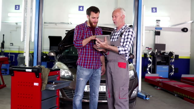 Senior mechanic at work in his garage with custom video
