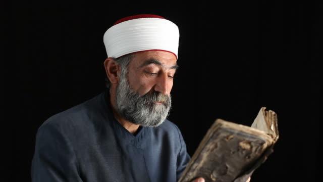 Senior muslim imam reading in dark video