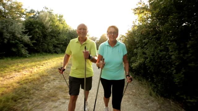 senior nordic walking couple smiling into cam video