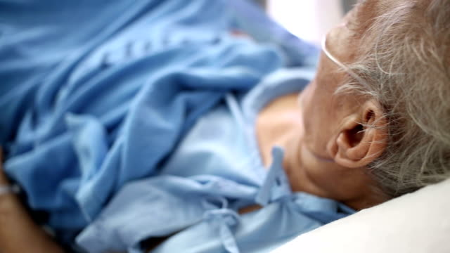 Senior Patient in bed breathing oxygen mask video