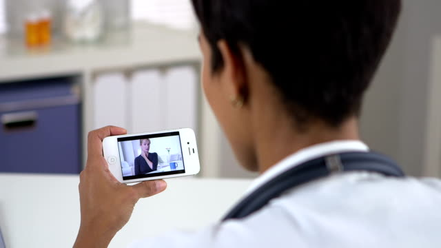 Senior patient video chatting with doctor on iphone video