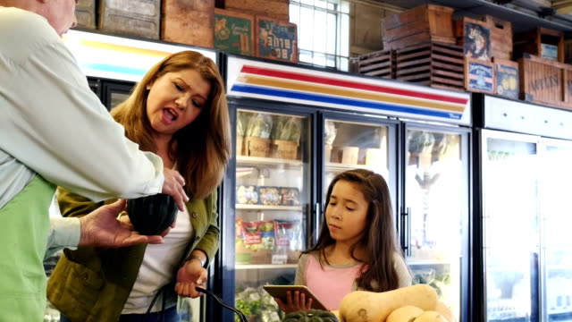 Senior produce clerk explains texture of squash to Hispanic mother and daughter video