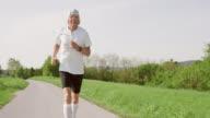 SLO MO TS Senior runner jogging on asphalt road video