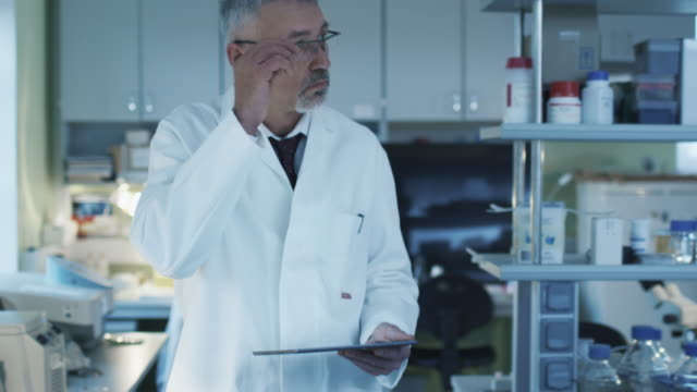 Senior scientist is walking with a tablet in a laboratory where colleagues are working. video