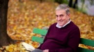 Senior smiling man reading a book in the park video