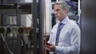 Senior technician checking server racks and walking away video