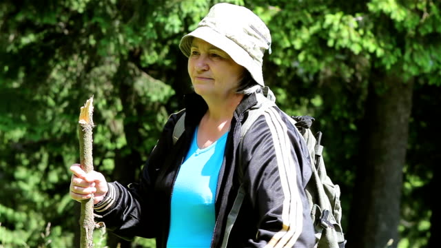 Senior tourist woman walking in the forest video