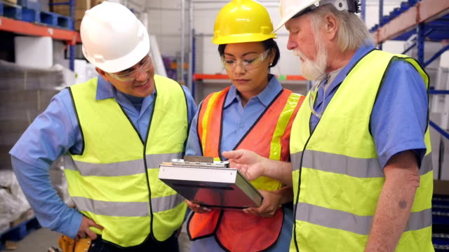 Senior warehouse manager training employees for shipping and distribution inventory video
