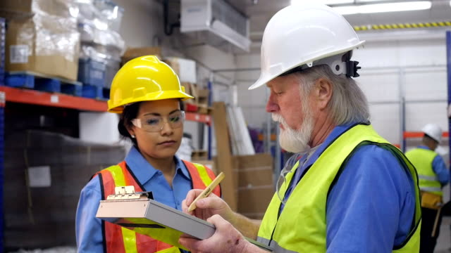 Senior warehouse manager training new female blue collar employee video