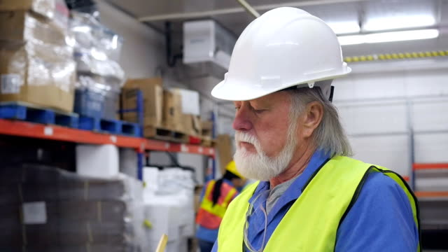 Senior warehouse worker taking inventory and smiling at camera video