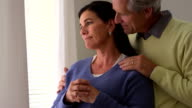 Senior wife grieving by window with husband video