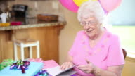 Senior woman at birthday party talks on cell phone video