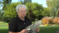 Senior woman at park reading newspaper video