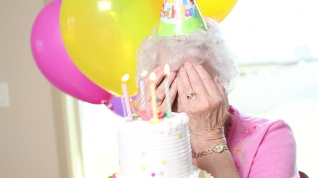 Senior woman blows out candles video