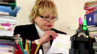 Senior woman bookkeeper in glasses and with commercial papers video