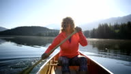 Senior Woman canoeing on a pristine lake video