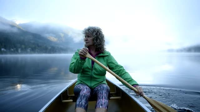 Senior Woman canoeing on a pristine lake video