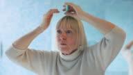 senior woman checking hairline for hair loss video