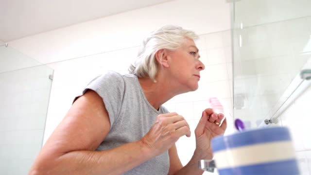 Senior Woman Checking Skin In Bathroom Mirror video