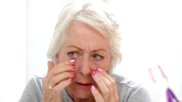 Senior Woman Checking Skin In Bathroom Mirror video