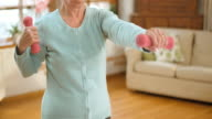 SLO MO senior woman doing hand weights exercises at home video