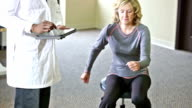 Senior woman doing physical therapy, doctor with digital tablet video