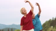 SLO MO Senior woman exercising in the park with her husband video