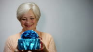 Senior woman expresses the joy of receiving a gift video