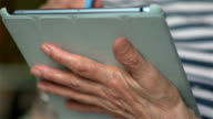 Senior woman hands holding tablet computer video