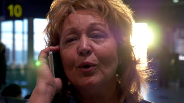 Senior woman having a vivid phone talk at airport video