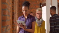 Senior woman helping female coworker with tablet in office hallway video