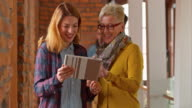 Senior woman helping younger coworker with tablet in office hallway video
