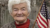 Senior Woman Holding American Flag Looking at Camera and Smiling video