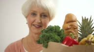 Senior woman holding bag of groceries video